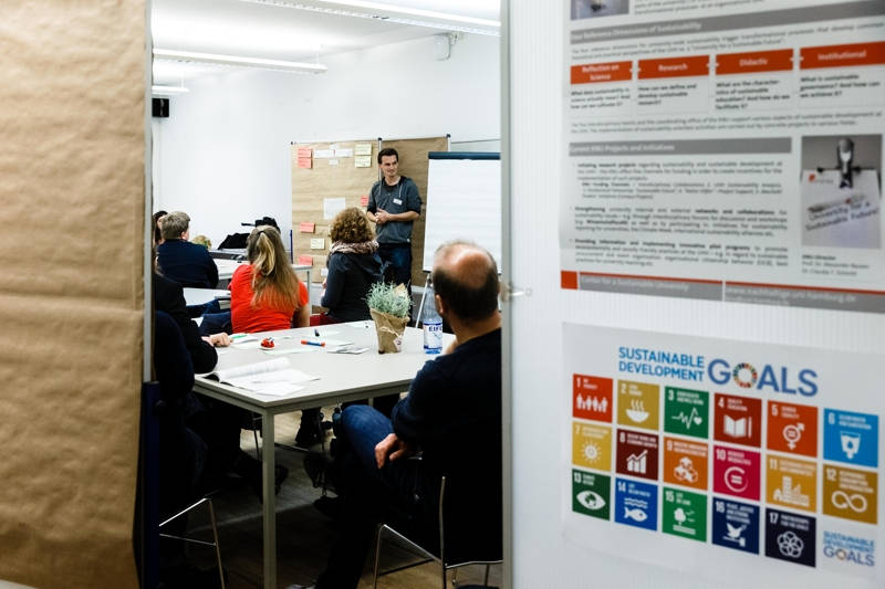 Presentation in the background, sdg poster in foreground